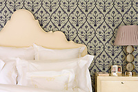 Detail of the cream headboard against the blue and grey patterned wallpaper of the master bedroom