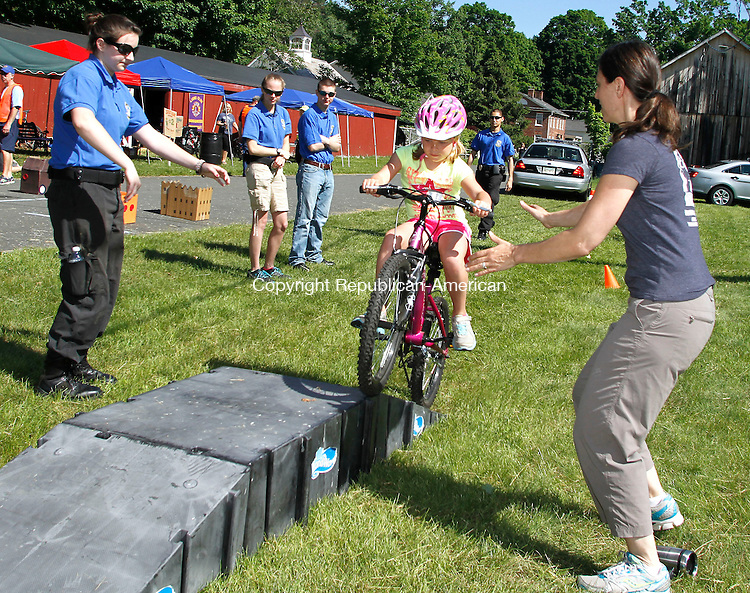 RIVERTON CT.- 01 JUNE 2014 - 060114JW03 - Cadet Thalia Byrne and volunteer Donna Labbe make ready to catch Addilyn Lefkowski age 4 as she attempts to to ride up the ramp as part of the bike rodeo during the Bike Bash Fundraiser Sunday morning.<br /> Jonathan Wilcox Republican-American