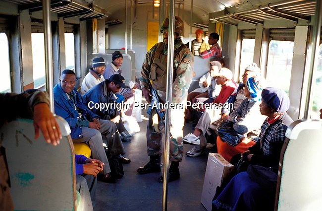 ditrtra00064 .Transport, trains. Unidentified soldiers searching for stolen goods and drugs  on a commuter train that travels from Cape Town to Khayelitsha on August 14, 2001 in Site B Khayelitsha, a township about 35 kilometers outside Cape Town, South Africa. Khayelitsha is one of the poorest and fastest growing townships in South Africa. People usually come from the rural areas in Eastern Cape province to find work as maids and laborers. Most people don't find work and the unemployment rate is very high, together with lot of violence and a growing HIV-Aids epidemic itÕs a harsh area to live in..©Per-Anders Pettersson/iAfrika Photos.