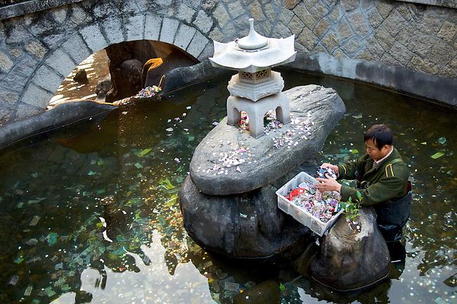 Un homme recoltant l'argent lance dans un bassin du temple bouddhique Nanputuo-Si a Xiamen. Province du Fujian/Chine/