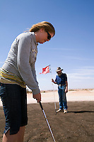 Playing golf at the Coober Pedy Opal Fields Golf Club.  The unique desert course is completely grassless with fairways of bare earth and putting greens made from oiled sand.  Coober Pedy, South Australia, AUSTRALIA.
