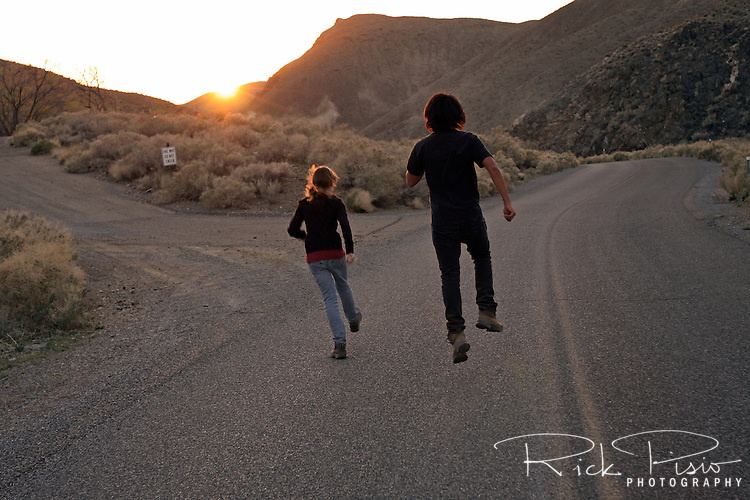 Big brother and younger sister skipping along a desert road into the sunset.