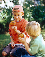 Two boys eating chocolate chip muffins in dappled sunlight in the garden