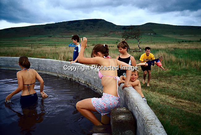 Youths bathing in a water cistern in a rural area in Blood River, Natal Province, South Africa after celebrating the battle of Blood River. Held on December 16th, the anniversary is the most important holiday in the Afrikaner calendar.(Photo by: Per-Anders Pettersson)