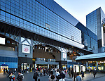 Kyoto Station, Kyoto-eki, modern glass building busy with people in the evening, second largest train station building in Japan. Shimogyo-ku, Kyoto, Japan 2017.
