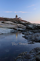 Tidepools reflect the Beavertail Lighthouse.