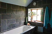 The simple and functional bathroom lined in grey slate tiles