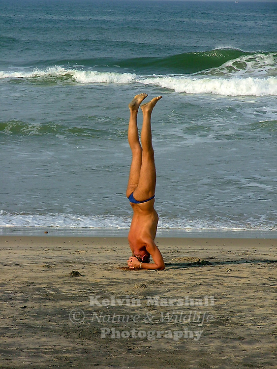 A tourist on the beach showing an Upside-Down Yoga Pose.