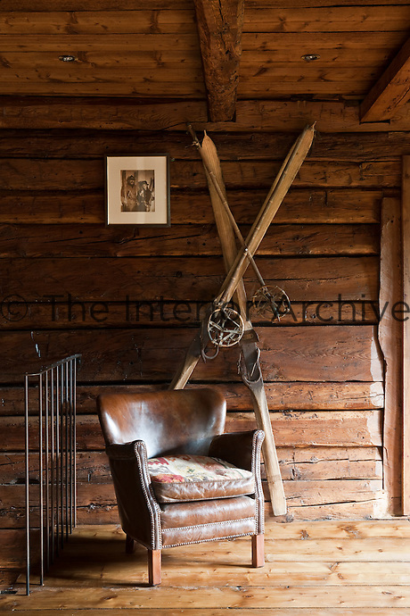 A pair of vintage skis is displayed on the rough wall of the landing