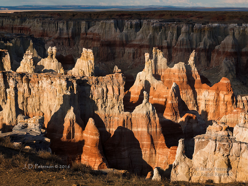 Coal Mine Canyon at Sunset, Arizona © 2016 James D Peterson.  A beam of warm light breaks through scattered clouds, casting long shadows that highlight these rugged hoodoos.  This Northern Arizona landscape is somewhat reminiscent of Utah's Bryce Canyon.