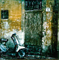 Modern scooter stands ready by the ancient door on a street in Florence.<br />