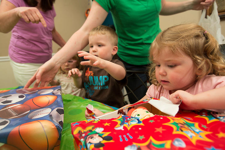 On her third birthday, Katelyn tears open a present while her mom, center, and grandmother, left, try to keep everything organized.