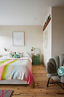 The master bedroom has a simple, retro feel and is decorated in neutral with scrubbed, wooden floorboards. A rainbow coloured bed cover provides a splash of colour.
