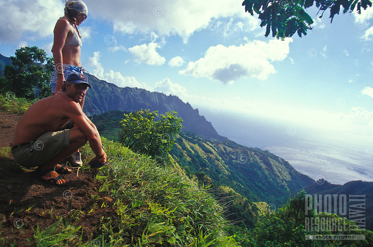 Couple looking at view of ocean while hiking across mountainous island