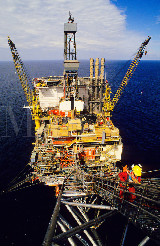 Offshore oil industry. Specialised engineers working on the flare tip of an offshore oil production platform in the North Sea, hundreds of feet above the sea. .