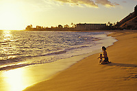 Mother and baby enjoying the sunset at Makaha Beach on Oahu's west shore