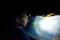 A paddler reads a map by headlamp at a backcountry campsite at Isle Royale National Park.