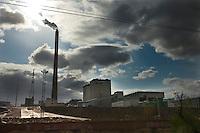 Daytime landscape view from a train of a commercial factory building site with smokestacks near Dàtóng Shì Chéng Qū in Shānxī Province, China  © LAN