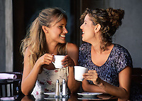 Portrait of two smiling women as they talk over coffee at a cafe.