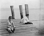 Lakewood NY: Two boys with stick poles fishing in Lake Chautauqua - 1901. Photographs taken during a church field trip to Chautauqua Institution in New York (Lake Chautauqua). The Stewart family and friends visited Chautauqua during 1901 to hear Stewart relative, Dr. S.H. Clark  speak at the institute. Alice Brady Stewart chaperoned and Brady Stewart came along to photograph the trip.  The Gallery provides a glimpse of how the privileged and church faithful spent summers at Lake Chautauqua at the turn of the century.