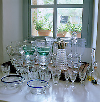 A collection of glass bowls, jugs, wine glasses and decanters is displayed on a window sill in the kitchen