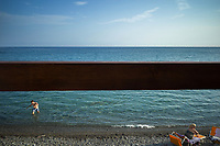 Italy. Liguria Region. Ospedaletti. An elderly woman seats on a chaise-longue on a stone beach on the Mediterranean sea. A man is coming out of the water. Summertime and holiday. Liguria is a region of north-western Italy. Ospedaletti is a comune (municipality) in the Province of Imperia. 28.07.2020 © 2020 Didier Ruef