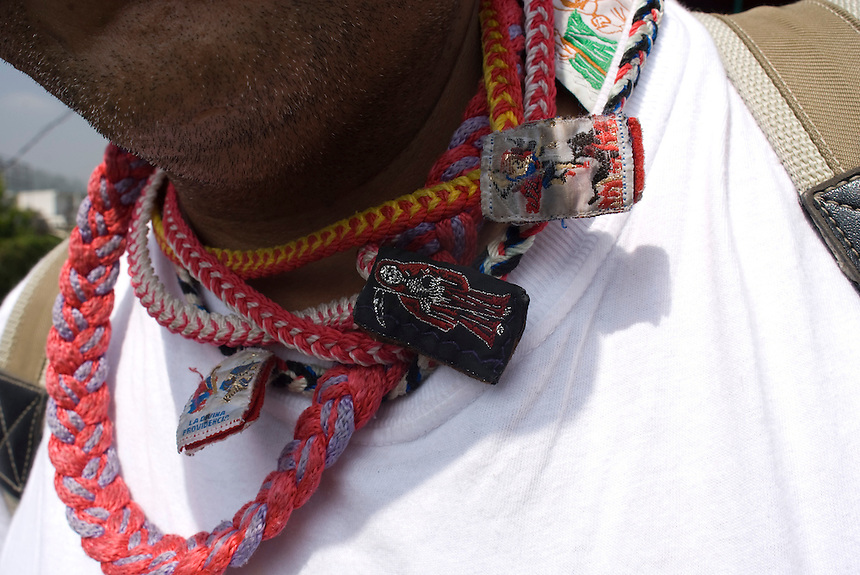 A man wears escapularios; religious icons, including the Santa Muerte or Saint Death for protection.  Mexico DF, 09-08-07