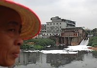 Chemical froth floats on black and dead Tangxia River is filled with industrial waste in Guangdong Province, China. Tangxia is a heavily polluted town..20 Mar 2007