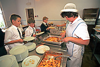Schoolchildren waiting in line for their school dinners. The dinner ladies are serving them hot food in the school canteen. This image may only be used to portray the subject in a positive manner..©shoutpictures.com..john@shoutpictures.com