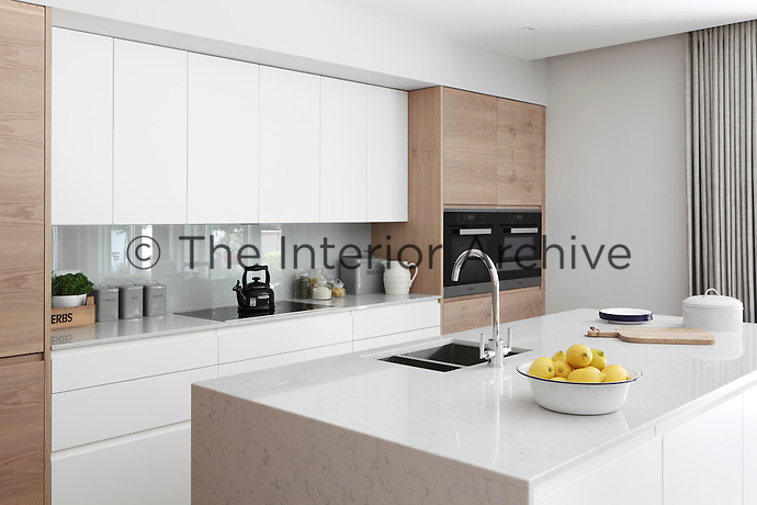 A minimal, contemporary kitchen with handleless white units for extra simplicity and glossy work surfaces to reflect the light from the patio doors