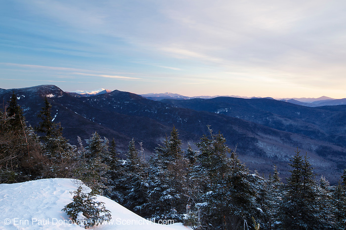 Mountain landscape from Mount Tecumseh in Waterville Valley, New Hampshire during winter months. The snow-capped Mount Washington is off in the distance.