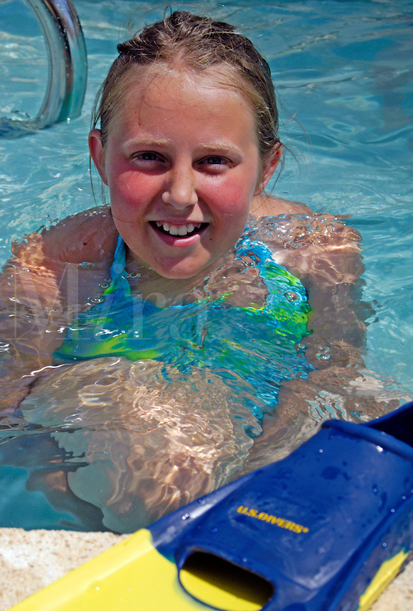 Young girl (MR) getting ready to snorkel in a swimming pool with her fins.