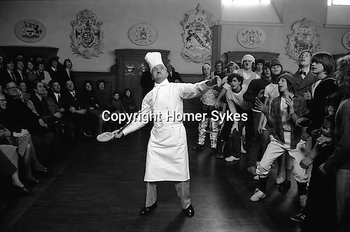 Westminster School annual Shrove Tuesday Pancake Greaze Westminster, London, England 1976. Head Chef Sam Sellars. tosses the pancake. Boys scramble for a piece of the pancake.<br />