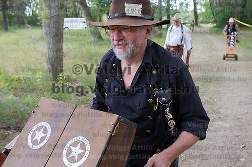 Competitor carries his gun box after his competition finished during the Cowboy Action Shooting European Championship in Dabas, Hungary on August 11, 2012. ATTILA VOLGYI