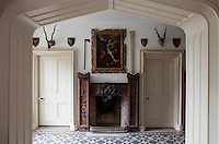 The entrance hall has a crenellated fire surround flanked by a pair of doors