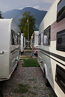 Switzerland. Canton Ticino. Tenero. Camping Campofelice. A young girl plays in the middle of caravans. A caravan, travel trailer, camper or camper trailer is towed behind a road vehicle to provide a place to sleep which is more comfortable and protected than a tent. It provides the means for people to have their own home on a journey or a vacation. Campers are restricted to designated sites for which fees are payable. 20.07.2018 © 2018 Didier Ruef