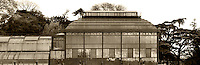 Plant History Glasshouse (formerly Australian Glasshouse), 1830s, Rohault de Fleury, and the adjacent incubators, Jardin des Plantes, Museum National d'Histoire Naturelle, Paris, France. Sepia coloured panoramic view of the glass and iron structure with the trees of the Botanical Garden in the background.