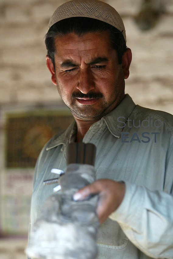 A gunsmith checks the barrels of a newly manufactured double barreled shotgun in his workshop in Pakistan's most prominent arms producing village of Darra Adam Khel, Pakistan, Thursday, October 19, 2006. Darra is a dusty, Wild West-type town, crawling with intelligence agencies, drug smugglers and gun-toting Pathan tribesmen. Darra-built Kalashnikovs, not known for their durability, sell for US$30 to US$45 alongside knuckledusters, shotguns with telescopic sights and twelve bores made to look like M16 assault rifles. Much of the weaponry is made from scrap metal from shipyards. Pakistan's government's attempts to regulate the Darra weapon industry always ended in failure. Photo by Simon Lim/Pictobank.