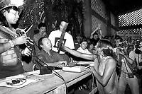 A índia Tuíra Kayapó ameaça, com um facão o diretor da Eletronorte, José Antônio Muniz Lopes, em protesto pela construção  da hidrelétrica de Kakarao, hoje Belo Monte, <br /> I Encontro das Nações Indígenas do Xingu<br /> Altamira, Pará, Brasil.<br /> Foto Paulo Jares<br /> 1989