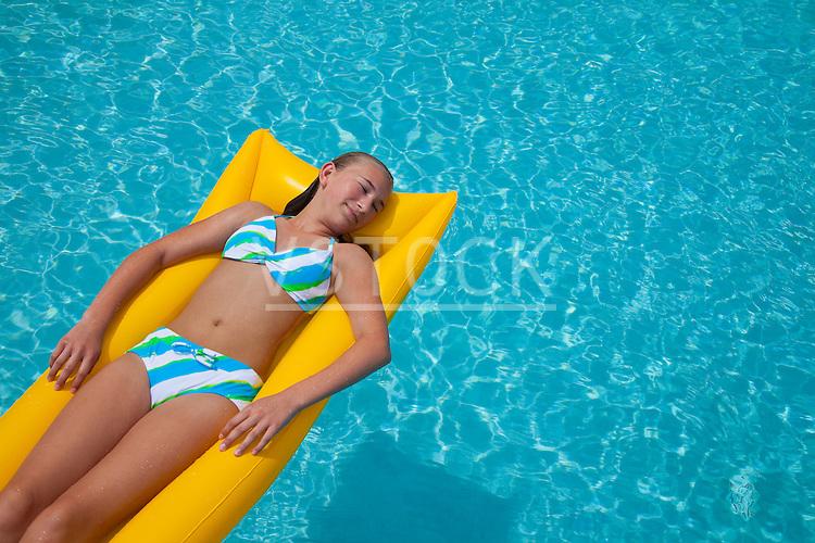 USA, Florida, St. Petersburg, girl (12-13) floating on water in pool raft