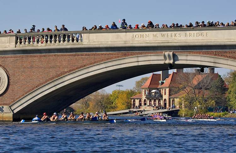 Boston, women rowers racing, 2006 Head of the Charles Regatta, Cambridge, Massachusetts, USA. Saturday October 21, 2006, Club Eights Women rowing beneath the Weeks Foot Bridge, Harvard University's Weld Boathouse in the distance,