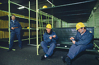 Switzerland. Canton Lucerne. Two men with yellow helmets play cards seated on bunk beds in the Sonnenberg tunnel in Lucerne during the largest civil defense exercise ever held in the country. Another man is bored and stands up alone. From 16 to 21 November 1987, almost 1200 men and women converted a motorway tunnel into perhaps the world's largest bunker structure. The civil protectors had to prove during the exercise «Ameise» ( Ants in english) that in an emergency more than 20,000 inhabitants of the city of Lucerne could survive here in the mountain for two weeks. The Sonnenberg Tunnel is a 1,550m  long motorway tunnel, constructed between 1971 and 1976. At its completion it was also the world's largest civilian nuclear fallout shelter, designed to protect 20,000 civilians in the eventuality of war or disaster. Based on a federal law from 1963, Switzerland aims to provide nuclear fallout shelters for the entire population of the country. The construction of a new tunnel near an urban centre was seen as an opportunity to provide shelter space for a large number of people at the same time. The giant bunker was built between 1970 and 1976 at a cost of 40 million Swiss francs. The shelter consisted of the two motorway tunnels (one per direction of travel), each capable of holding 10,000 people in 64 person subdivisions. A seven story cavern between the tunnels contained shelter infrastructure including a command post, an emergency hospital, a radio studio, a telephone centre, prison cells and ventilation machines. The shelter was designed to withstand the blast from a 1 megaton nuclear explosion 1 kilometer away. The blast doors at the tunnel portals are 1.5 meters thick and weigh 350 tons. The logistical problems of maintaining a population of 20,000 in close confines were not thoroughly explored, and testing the installation was difficult because it required closing the motorway and rerouting the usual traffic. The only large-scale test, a five-day exercise in