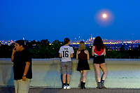 EAGLE ROCK, NJ - JUNE 09: People take a look of the Strawberry Moon as it rises over lower Manhattan on June 06, 2017 in Montclair, New Jersey. Photo by VIEWpress/Eduardo MunozAlvarez
