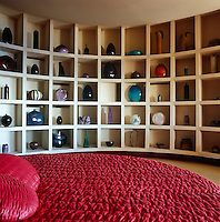 In one of the round bedrooms floor-to-ceiling shelving displays a collection of vases