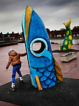 Child playing amongst the fish sculptures that have been installed in the town centre of Breskens, The Netherlands. As a celebration of the port's once prosperous fishing industry.<br />