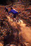 A picture of a man riding a mountain bike through backlit dust on a dry summer day.