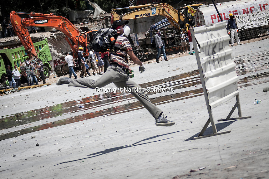 In this Tusday, Jun. 11, 2013 photo, a protester throws a stone to the anti-riot police duriing clashes at the streets of Taksim Square in Istanbul,Turkey. (Photo/Narciso Contreras).
