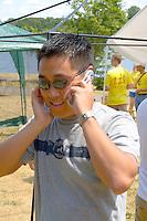 Intense Asian American man age 23 talking on his cell phone. Dragon Festival Lake Phalen Park St Paul Minnesota USA