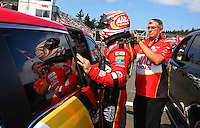 Aug. 4, 2013; Kent, WA, USA: A crew member helps NHRA top fuel dragster driver Doug Kalitta get suited up before first round of eliminations during the Northwest Nationals at Pacific Raceways. Mandatory Credit: Mark J. Rebilas-USA TODAY Sports