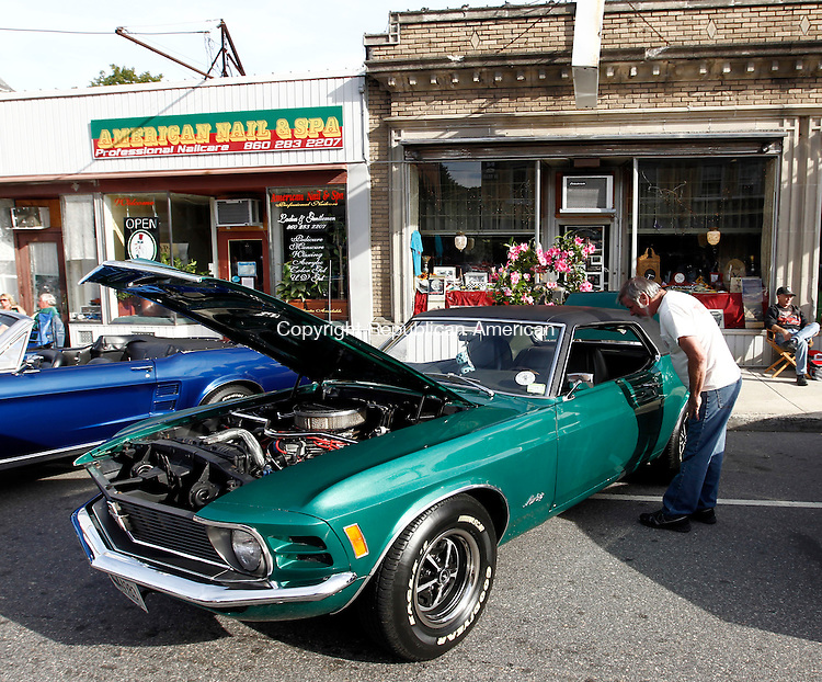 Thomaston, CT- 14 September 2014-091414CM13-  Dan Kinaney of New Hartford checks out the interior of a classic Ford Mustang during The Thomaston Police Department's Main Street Summer Cruise on Sunday. The event, which was started 16 years ago, is held to raise money for its Police Explorers program.  Christopher Massa Republican-American